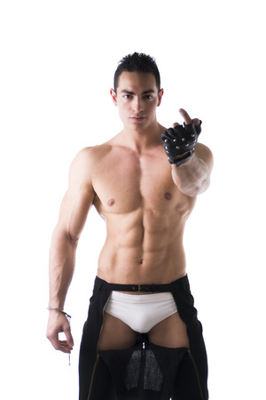 Muscular shirtless young man with handcuffs and studded glove inviting to get closer with his finger