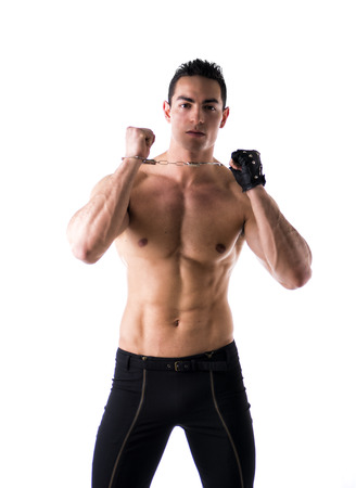 Muscular shirtless young man with handcuffs and studded leather glove, isolated on white photo