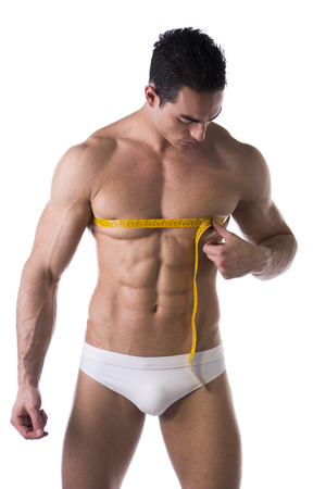 Muscular shirtless young man measuring chest and pecs with tape measure, looking at torso, isolated on white photo