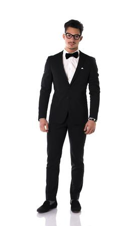 Elegante joven guapo con traje y corbata de lazo, foto de cuerpo entero