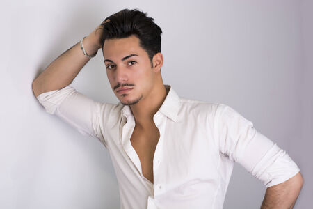 Elegant attractive young man with white shirt, leaning against wall photo