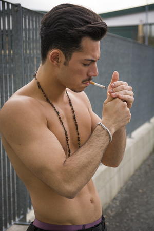 Athletic shirtless young man with mustache and necklace, lighting a cigarette photo