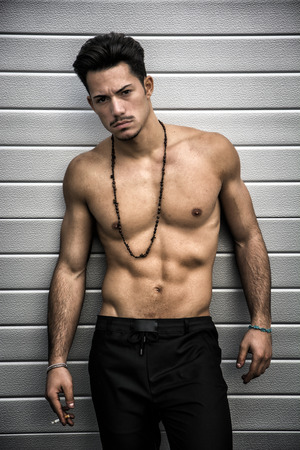 Athletic shirtless young man with mustache and necklace, smoking a cigarette Stock Photo