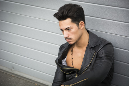 Young man with black leather jacket looking away, sitting on the ground outdoors photo
