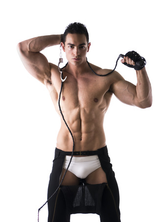 Muscular shirtless young man with handcuffs, whip and studded glove on white background photo