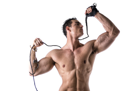 strip tease: Muscular shirtless young man with handcuffs, whip and studded glove on white background