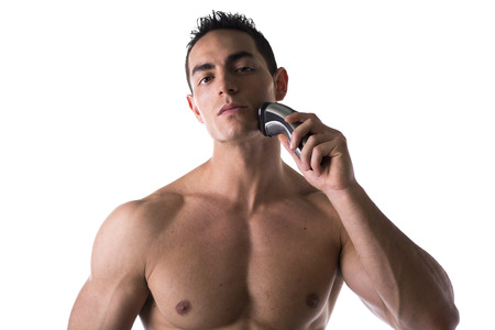 Muscular man shirtless using electric shaver, looking at camera, isolated on white photo