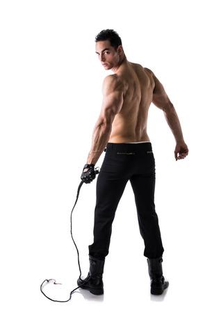 sin camisa: Joven sin camisa muscular con el látigo y guantes tachonados, foto de cuerpo entero de la parte posterior