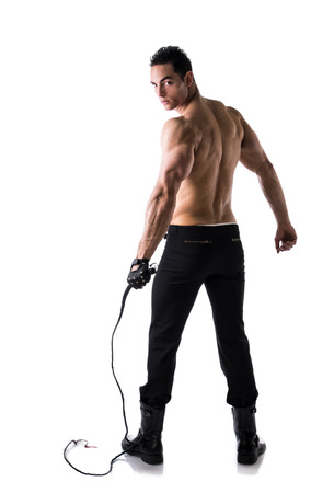 Muscular shirtless young man with whip and studded glove, full length shot from back
