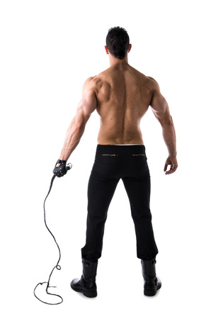 Back of muscular shirtless young man with whip and studded glove on white background, full body shot