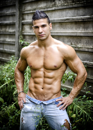 hunk: Muscular young latino man shirtless in jeans in front of concrete wall, with hands on hips