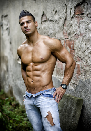 Muscular young latino man shirtless in jeans in front of concrete wall, looking at camera photo