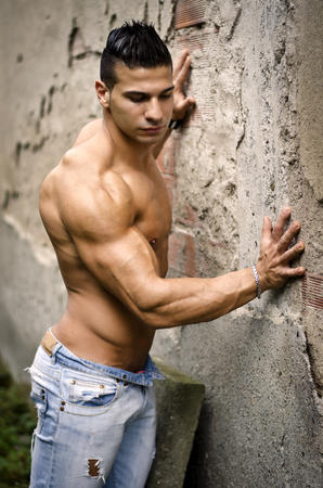 latino man: Muscular young latino man shirtless in jeans leaning against concrete wall, looking off camera