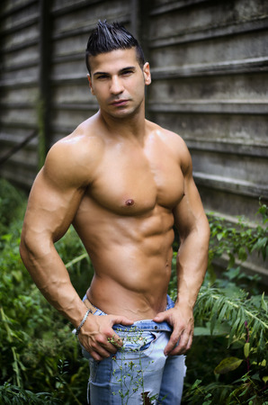 Muscular young latino man shirtless in jeans in front of concrete wall looking at camera photo