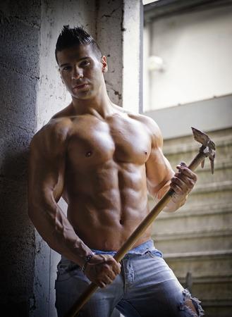 農具ジーンズで汗をかく彼の手で保持している筋肉の上半身裸の若い男