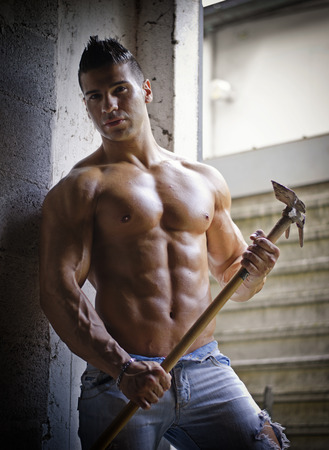 Muscular shirtless young man holding farming tool in his hands, sweaty in jeans