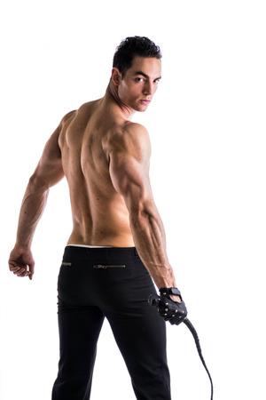 Muscular shirtless young man with whip and studded glove on white background from the back