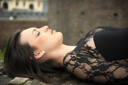 Pretty brunette young woman lying down on brick wall, with eyes closed photo