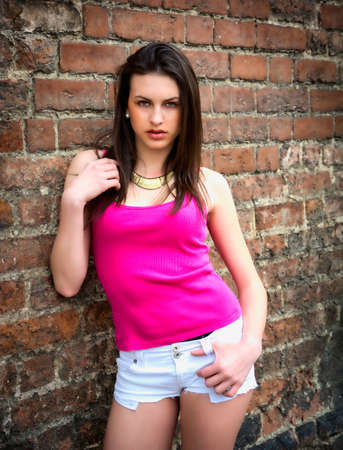 Pretty brunette girl against brick wall in casual clothes, looking at camera Stock Photo
