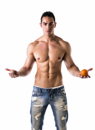 Muscular shirtless young man deciding between healthy fruit and unhealthy cookies photo