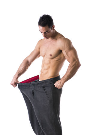 Shirtless young male bodybuilder has lost weight, wearing large pants photo