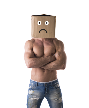 Muscular shirtless bodybuilder with sad, unhappy cardboard box on his head, isolated on white, arms crossed photo