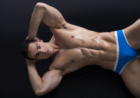 Attractive young muscle man laying on the floor with muscular ripped body