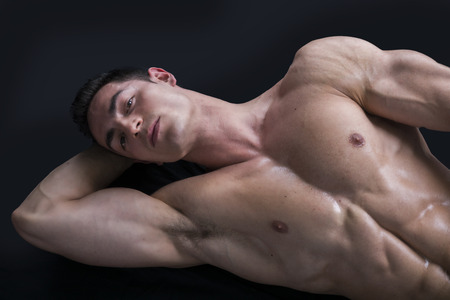 Attractive young muscle man laying on the floor with muscular ripped body photo