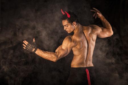 Nackter Oberkörper muskulösen männlichen Bodybuilder mit Teufel Kostüm auf dunklem Hintergrund gekleidet Standard-Bild