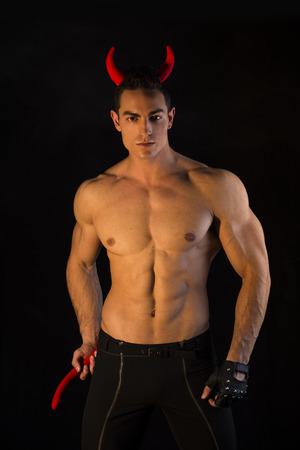 Shirtless muscular male bodybuilder dressed with devil costume on dark background