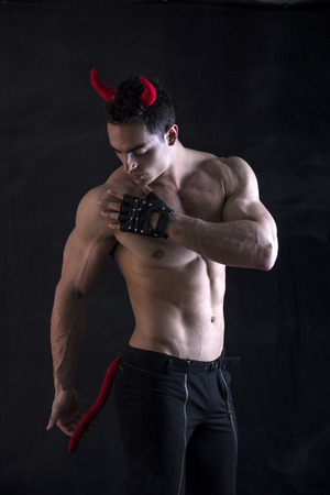 demon: Shirtless muscular male bodybuilder dressed with devil costume on dark background