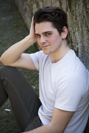 sitting on the ground: Attractive young man sitting on the ground against rock outdoors, looking at camera with a smile Stock Photo