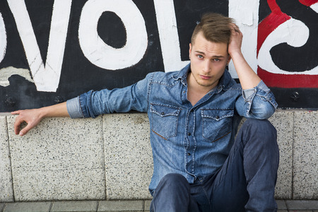 sitting on the ground: Attractive young blond man sitting against colorful graffiti wall, wearing denim shirt and jeans Stock Photo