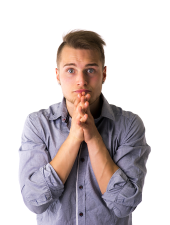 Needy, desperate young man pleading with hands joined as if praying to camera, isolated Stock Photo