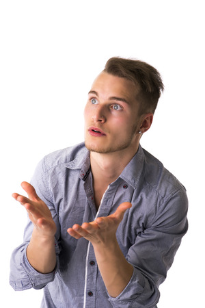 Needy, desperate young man pleading with hands open as if asking someone, isolated