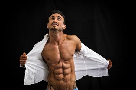 hombres musculosos: Bodybuilder masculino que saca su camisa revelando el torso musculoso, sobre fondo negro Foto de archivo