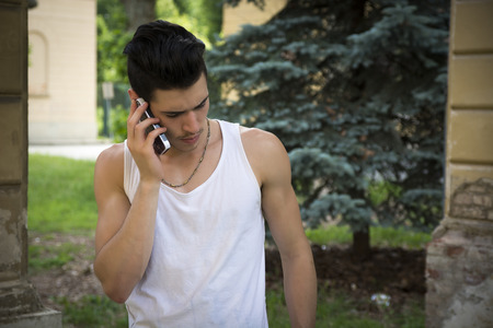 Handsome young man outdoors talking on cell phone in summer photo