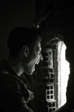 Young man indoor screaming out through hole in the wall, black and white shot photo
