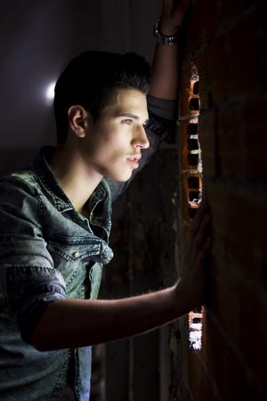 Handsome young man looking out through hole in brick wall photo