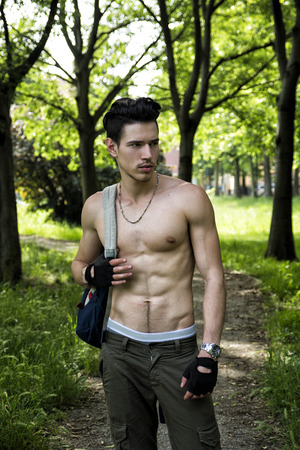 Handsome young man shirtless outdoors hiking on park path with backpack on shoulder photo