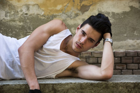 Attractive young man laying down, wearing white tank-top outdoors, looking at camera Stock Photo