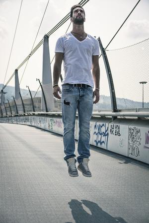 """Apuesto joven """"levitando"""" en el aire al aire libre en entorno urbano Foto de archivo"""