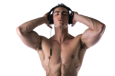 Muscular man shirtless, listening to music on headphones, with eyes closed, isolated photo