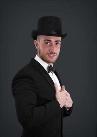 tophat: Attraente giovane uomo d'affari con il vestito, top-hat e bowtie su sfondo scuro