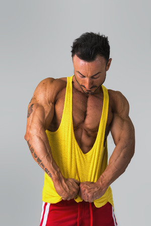 Bodybuilder pulling down tanktop on ripped muscular torso Stock Photo