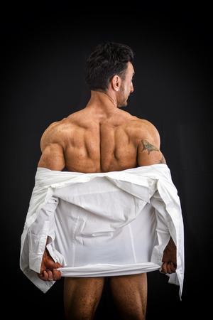 Male bodybuilder undressing revealing muscular back and shoulders, on dark background Stock Photo