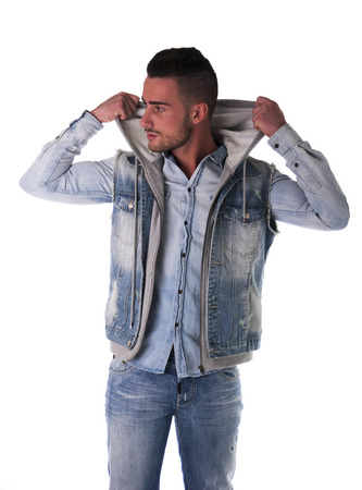 Handsome young man in hoodie, denim vest and jeans, isolated on white photo