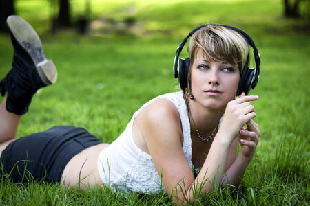 Beautiful young girl listening to music on her headphones as she relaxes in the garden or park lying on her stomach on the green grass photo