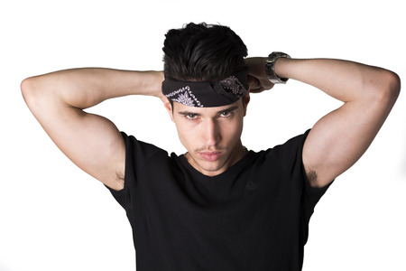 Handsome young man tying a bandanna around his head in the form of a headband photo