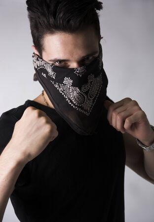 threateningly: Man with his face hidden behind a bandanna balling his fists aggressively and raising them threateningly as he stares balefully at the camera